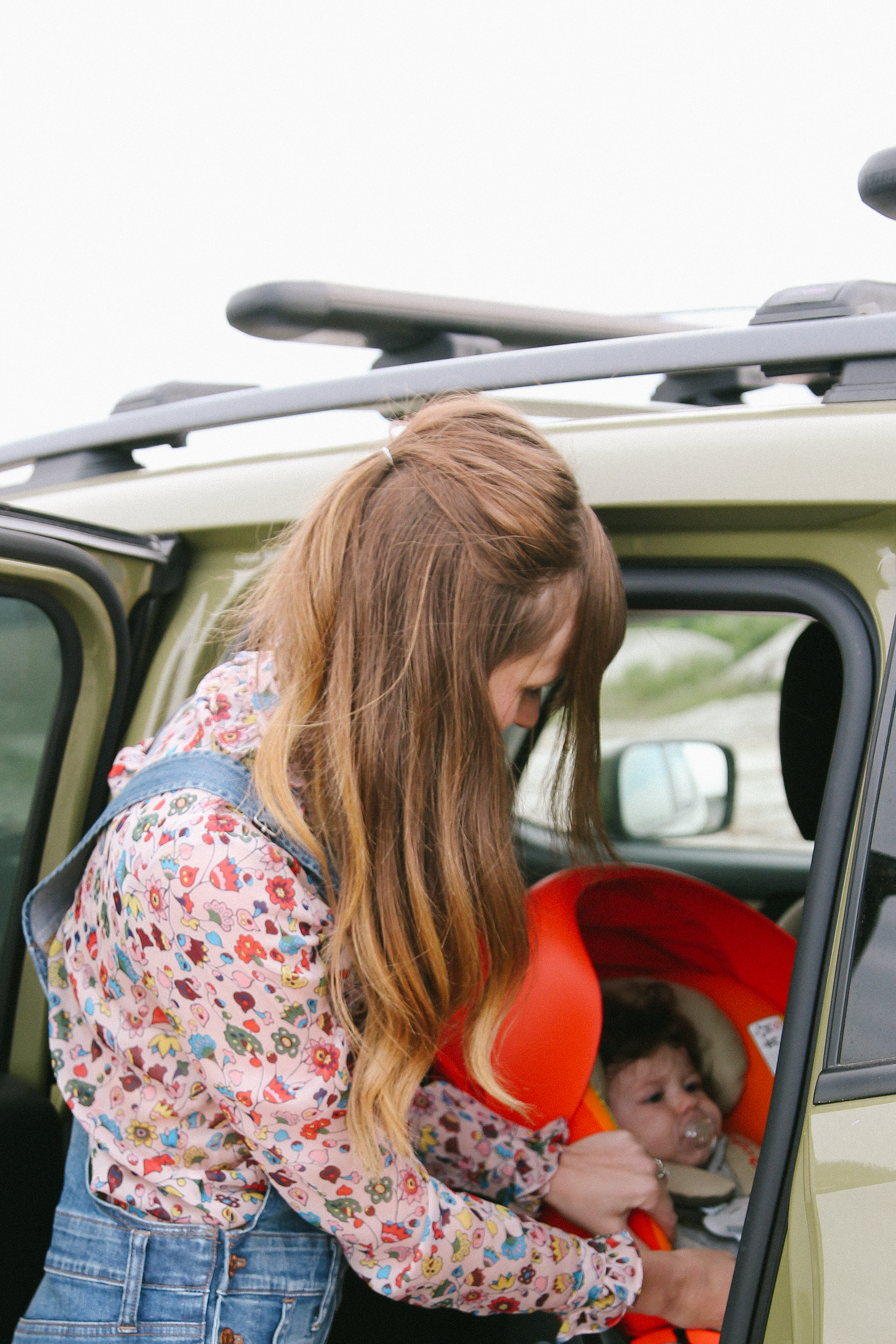 mom with carseat, roadtripping with a baby